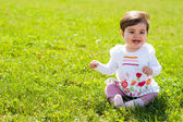 Little girl sit on grass with an open mouth smile — Stock Photo