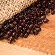 Coffee beans in burlap sack on wood — Stock Photo #12556825