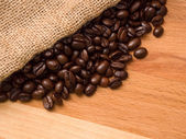 Coffee beans in burlap sack on wood — Stock Photo