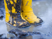 Yellow boots in puddle — Stock Photo