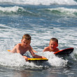 Two boys playing in surf — Stock Photo