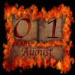 Stock Photo: Burning wooden calendar August 1.
