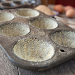 Buttered muffin tin with corn flour — Stock Photo