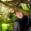 Young boy sitting in a tree smiling — Stock Photo