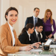 Stock Photo: Business woman smiling with colleagues in background
