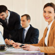 Business woman smiling with colleagues in background — Stock Photo #34709049