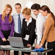 Business woman with colleagues looking at laptop — Stock Photo