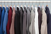 Display of man suits in a closet — Stock Photo