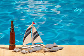Telescope, ship and textile stuffed fish next to the pool — Stock Photo