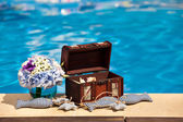 Flowers textile stuffed fish and treasure chest next to the pool — Stock Photo