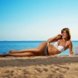 Luxury girl lies on the beach with laptop — Stock Photo #11291478