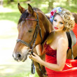Woman with bright makeup on the horse outdoors — Stock Photo #15445845