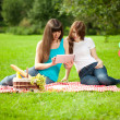 Two women in the park on a picnic and Tablet PC — Stock Photo