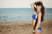 Young beautiful woman on the sand by the sea — 图库照片