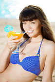 Beautiful woman with a drink in hand on the beach — Stok fotoğraf