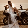 Bride sitting on a quad bike on the beach - Stock Photo