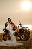 Bride sitting on a quad bike on the beach — Stock Photo