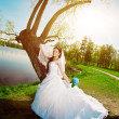 Bride on a field in the sunshine — Stockfoto