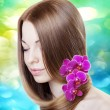 Woman with orchids in her gorgeous hair — Стоковая фотография