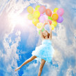 Woman holding balloons against sun — Stock Photo #27076123