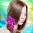 Woman with orchids in her gorgeous hair — Stock Photo #27076259