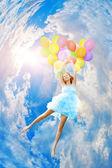 Woman holding balloons against sun — Stock Photo