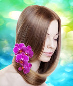 Woman with orchids in her gorgeous hair — Stock Photo