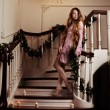 Rich woman on staircase with a candle — Stock Photo #27083091