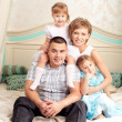 Happy family smiling at home — Stock Photo #27083265