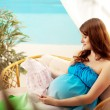 Pregnant woman on the beach in bungalow — Стоковая фотография