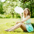 Stock Photo: Woman holding white bubble talk in summer park