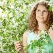 Young beauty woman in blooming garden — Foto Stock