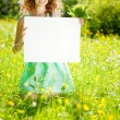 Woman holding white blank poster in summer park — Stock Photo
