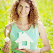 Young woman with hose model and key in a lush garden — Stock Photo #27086691