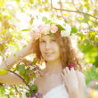 Young beauty woman in blooming garden — Stock Photo #27086789