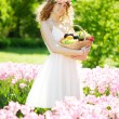 Cute young woman with a basket of fruit in hand — Stock Photo #27086847