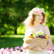 Woman with a basket of fruit in hand — Stock Photo