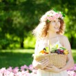 Stock Photo: Woman with a basket of fruit in hand