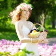 Woman with a basket of fruit in hand — Stock Photo #27086875