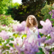 Young woman in blooming garden — Stock Photo #27086945
