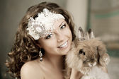 Luxury woman in fashion interior with bunny — Stock Photo