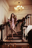 Rich woman on staircase with a candle — Stock Photo