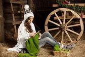 Woman in the village barn with knitting in hand — Stock Photo