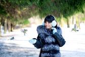 Jeune femme nourrir oiseaux hiver — Photo