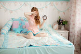 Cute young girl in nice children's bedroom with alarm clock — Stock Photo