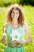 Young woman with hose model and key in a lush garden — Stock Photo