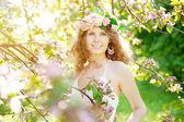 Unga skönhet kvinna i blommande trädgård — Stockfoto