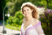 Young woman in blooming garden with wind in her hair — Stock Photo