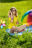 Stylish young woman listening to music in the park — Stock Photo