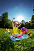 Beautiful young woman listening to music in the park — Stock Photo